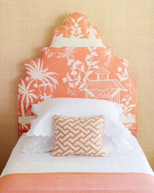 Twin bed with high coral colored upholstered headboard with a Chinoisserie print