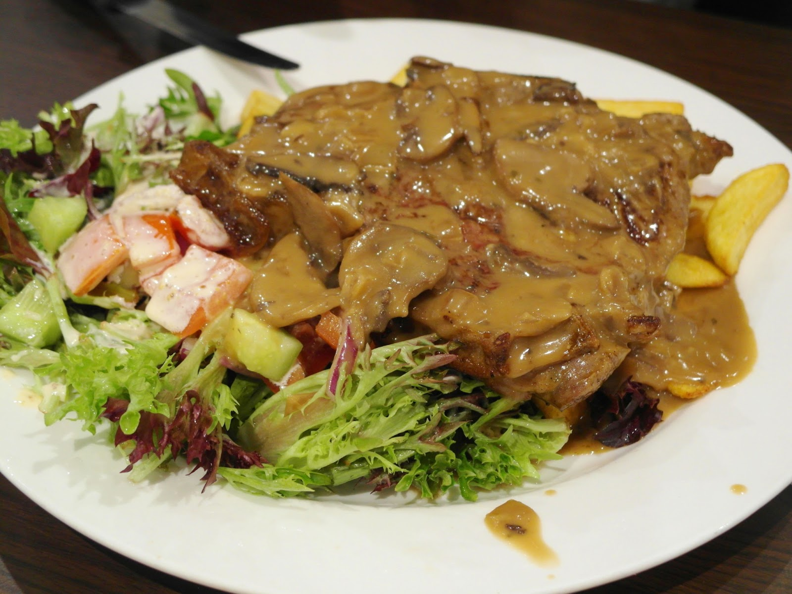 Medium cooked steak with mushroom sauce served with salad and chips i wish the steak had been thicker but i guess if it had been thicker there would be