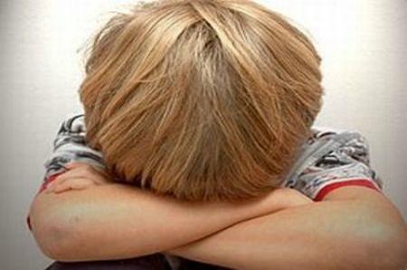 ولد صغير في صورة وهو يبكي على يديه دون أن يظهر وجهه
