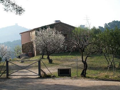 La masia de Can Palós Nou amb l'ermita de Sant Ramon al fons
