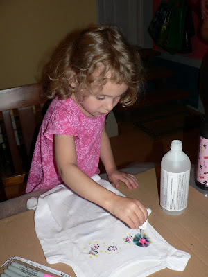 child using a dropper to squirt rubbing alcohol onto DIY tie-dyed shirts