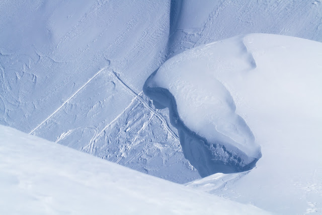 A giant cornice overhangs a skin track.