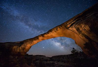 looking up at the milky way through the natural rock bridge in Utah