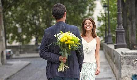أمور لا تثير إهتمام الرجال في العلاقات العاطفية! - رجل يقدم ورود لحبيبته امرأة - man holding flowers behind his back
