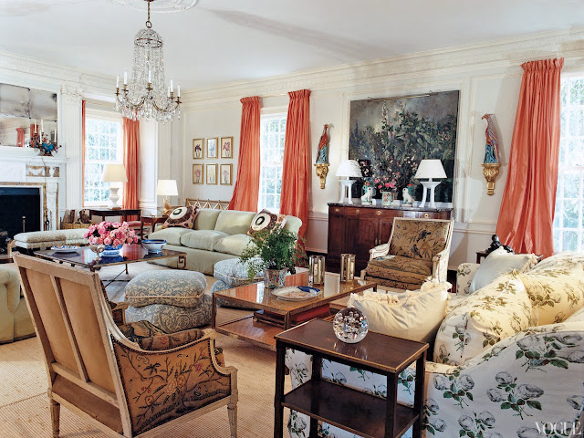 Living room with coral needlepoint louis XVI chairs, botanical printed sofa, coral curtains and a crystal chandelier