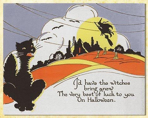Autumn imagery features field with corn shocks, cottage silhouette, a big black cat, and a witch over the moon.