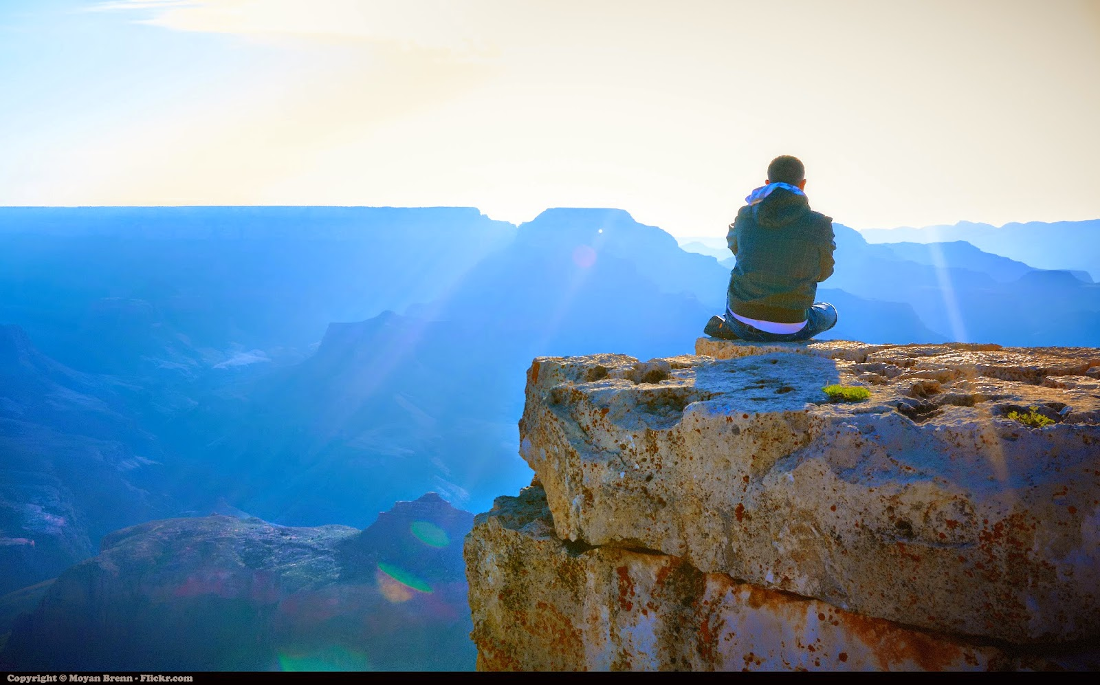 Meditation by Moyan Brenn: Man sitting on mountain top, looking at sunrise over valley.