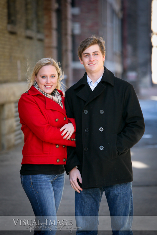 Engaged couple wearing winter coats in downtown Milwaukee brick alley