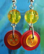 Long drop dangle earrings in yellow and orange have layered buttons hanging from large faceted beat