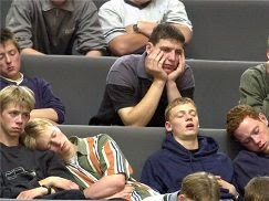 Students bored during a lecture. Some are asleep while others look extremely uninterested