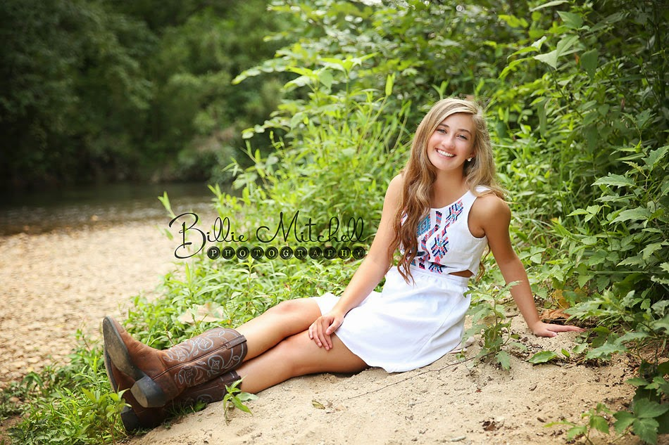 teen girl in white dress and cowboy boots sitting in the sand on the shore