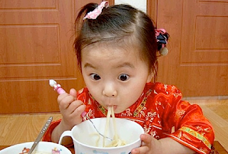funny picture: child is eating spaghetti