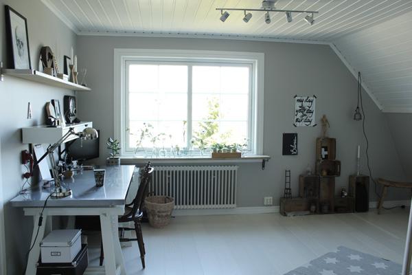 arbetsrum och ateljé i vitt och grått, skrivbord från ikea, vitt golv, hyllor med inredningsdetaljer