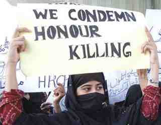 Veiled woman holds sign protesting honour crimes