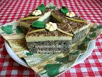 Citrompudingos bögrés mákos sütemény, reszelt csokoládéval megszórva a teteje, díszítésként virág és levél marcipán.