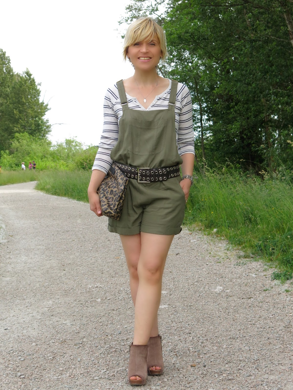 styling olive shortalls with a striped henley top, a wide belt, and wedge heels