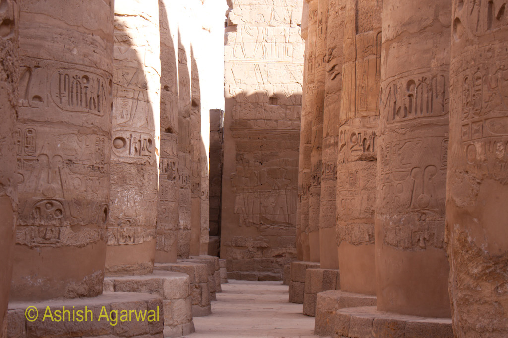 2 rows of carved pillars inside the Hypostyle Hall in the Karnak temple