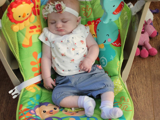 baby girl sleeping in fisher price swing sweat wearing rose headband jeans and floral top