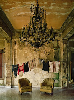 In a decadent, decaying mansion, laundry hang on clotheslines under an ornate chandelier. Is it decoration or necessity?