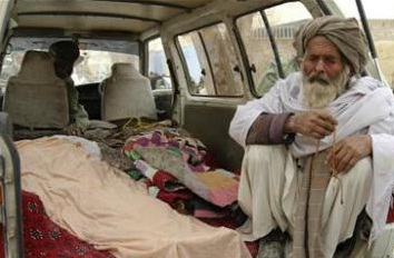 an Afghan man sits next to the dead bodies killed by US Army