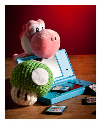 yoshi plushi with a nintendo DSi and game cartridges