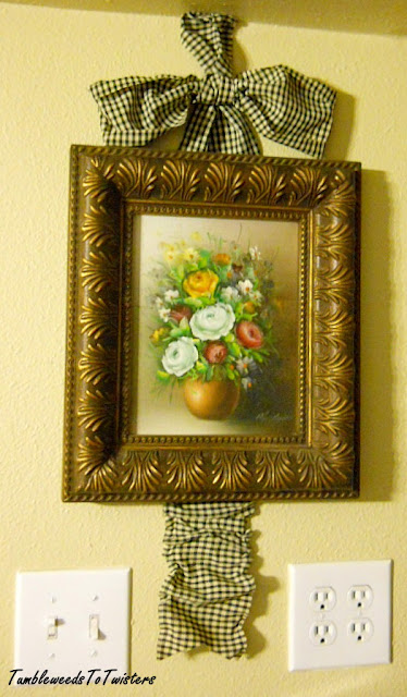framed floral oil painting with checkered ribbon bow and tail