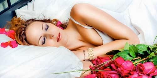 chica durmiendo en la cama con rosas