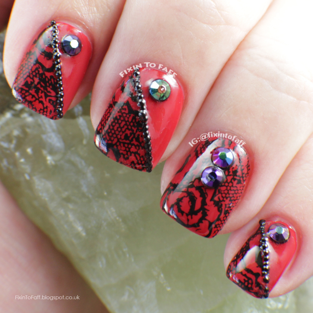 Red and black lace nails with AB rhinestones and microbead accents.