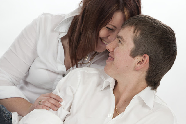 Young couple in white shirts turning towards each other.