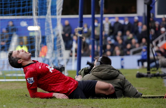 Manchester United player Robin van Persie looks uncomfortable after tumbling into a camera bunker