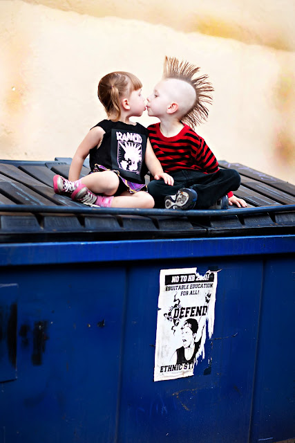 Young brother and sister kiss on dumpster during family photo session