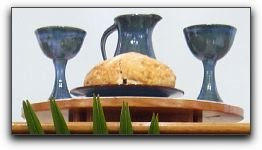 Communion bread, two chalices and a pitcher.