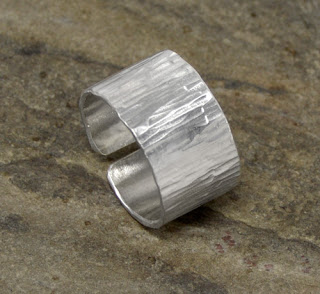 http://brackendesigns.com/product/textured-wide-band-sterling-silver-ring-open-back