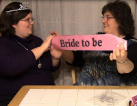 Two women unboxing a bride sash and tiara