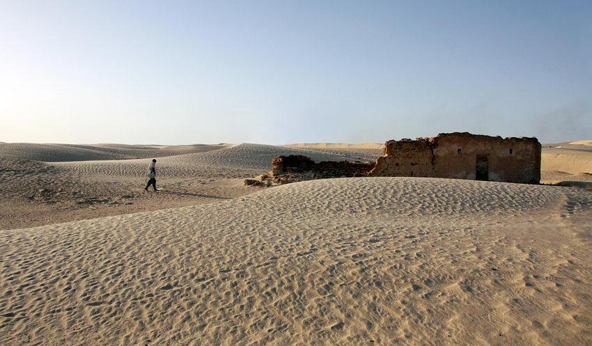Homem a caminhar para uma construção em ruínas no deserto