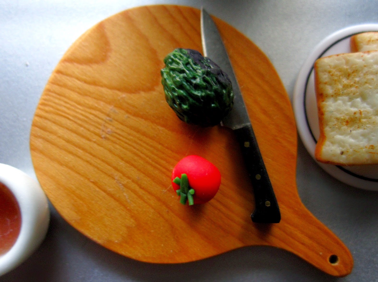 Modern dolls' house miniature chopping board with a knife, an avocado and a tomato on it. Next to it is a plate of toast and a mug of tea.