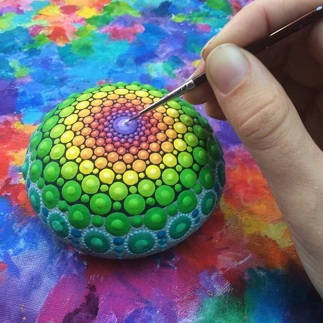 Artista convierte piedras de océano en diminutas mandalas al pintar coloridos patrones de puntos