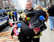 Boston firefighter James Plourde carries an injured girl away from the scene .