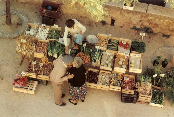 elderly man and woman kissing by a vegetable stall in a French market.