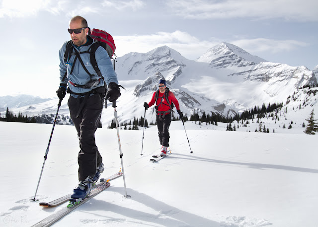 Two skiers skin across Little Yoho Valley with The President and Vice President in the background.