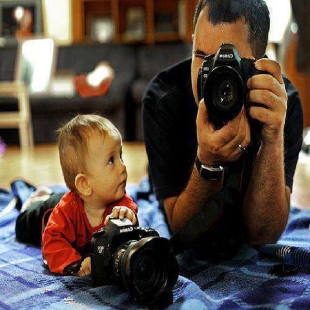 bébé qui regarde son papa photographier