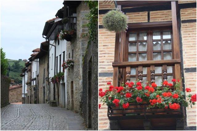Calle empedrada y balcón con flores en Santillana del Mar
