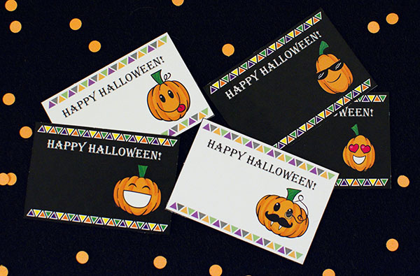 5 happy halloween emoji pumpkin tags on a black background with orange confetti