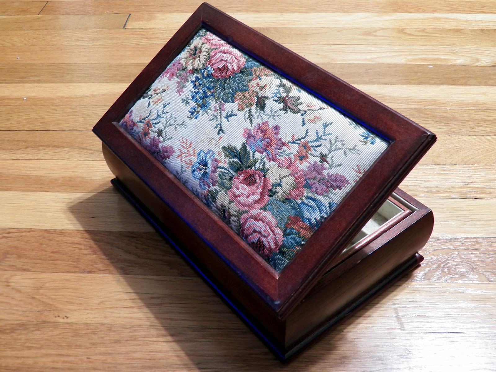 the jewelry box lid comprises the following layers from outside in a wooden frame tapestry and padding a backboard a layer of glue and a mirror