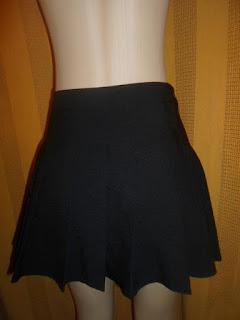 saia curta de pregas na cor preta tamanho médio.