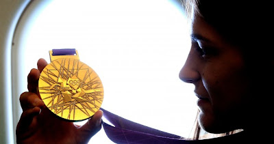 Katie Taylor examines her Olympic gold medal on her way home to Bray