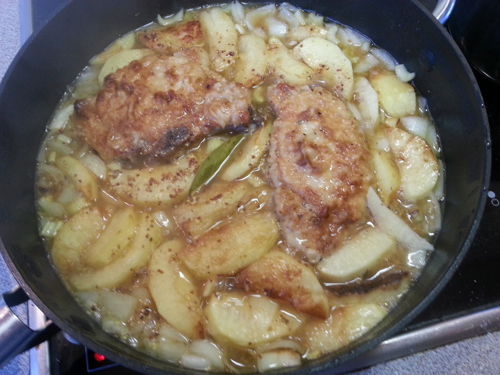 Braised pork and apples cooking in a pan