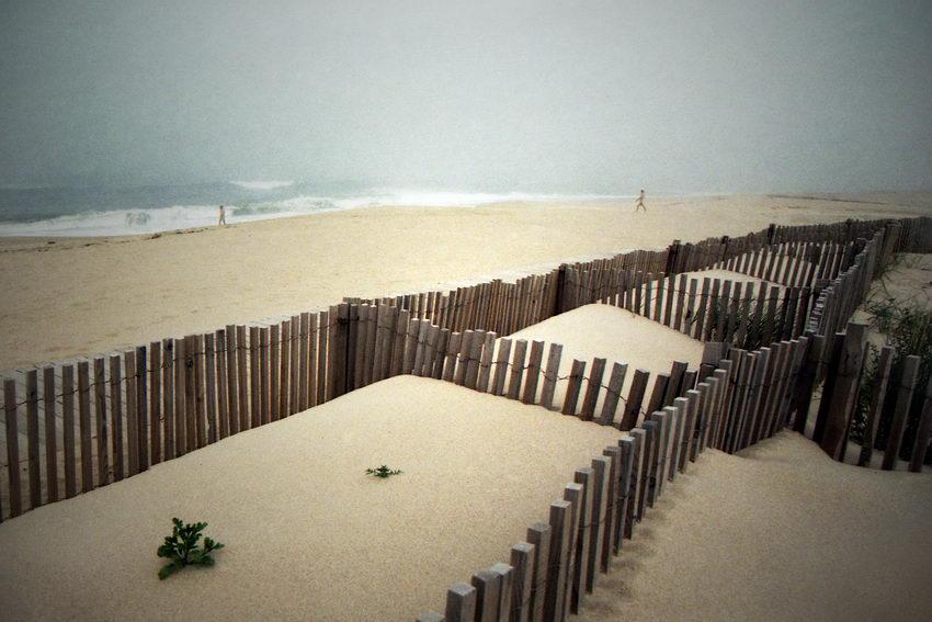 Fofo da praia com neblina e duas pessoas a caminhar para o mar. Em primeiro plano a protecção das dunas - ripas de madeira na vertical