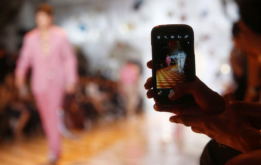 A model is pictured in a screen of a smartphone during the Versace men's Spring-Summer 2015 show, part of the Milan Fashion Week, unveiled in Milan, Italy, Saturday, June 21, 2014.