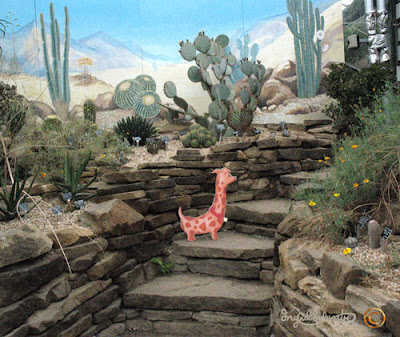Hals the Neckshund dog at the Secret Portal behind the Intergalactic Cacti The Neckmanns of Giraffe World Storytelling by North East Artist Ingrid Sylvestre at University of Durham Botanic Garden featuring her characters the Neckmanns in their World Artwork and Stories by Ingrid Sylvestre UK Artist & Writer